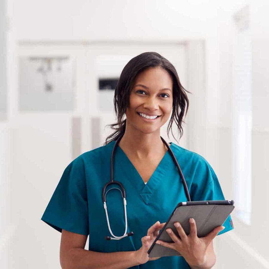 portrait-of-smiling-female-doctor-wearing-scrubs-KLLFEZS-1.jpg